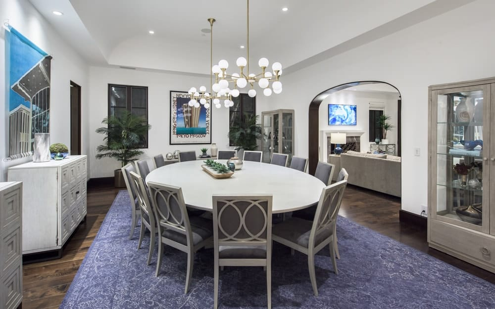 This is the formal dining room with a large white circular dining table surrounded by gray dining chairs and topped with round chandeliers. These are then complemented by the area rug on the dark hardwood flooring underneath. Image courtesy of Toptenrealestatedeals.com.