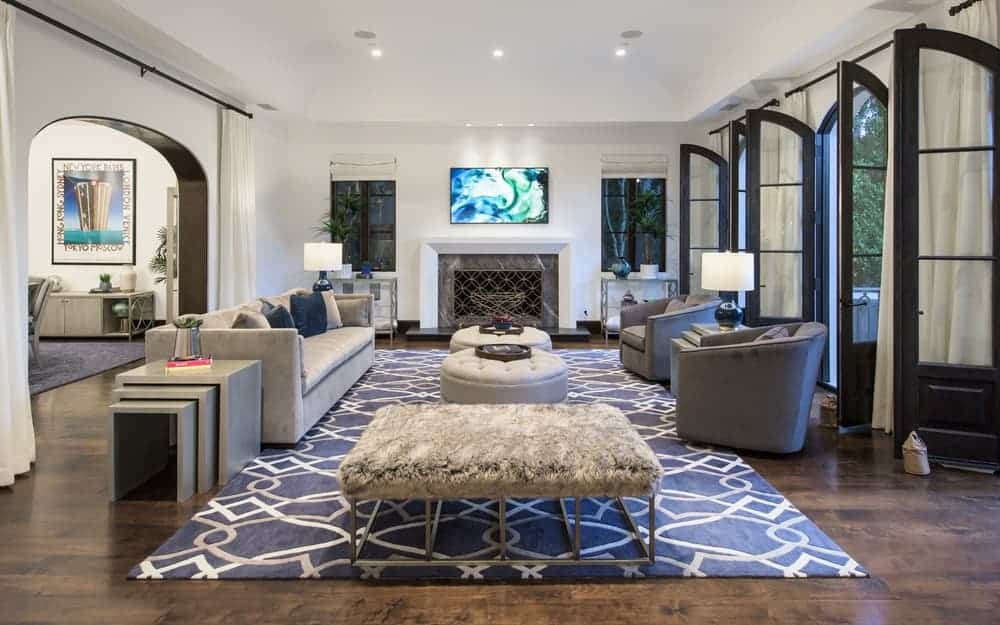 This is the family room with a sofa, a couple of cushioned armchairs and a couple of tufted ottomans for coffee table that stand out against the gray area rug. Image courtesy of Toptenrealestatedeals.com.