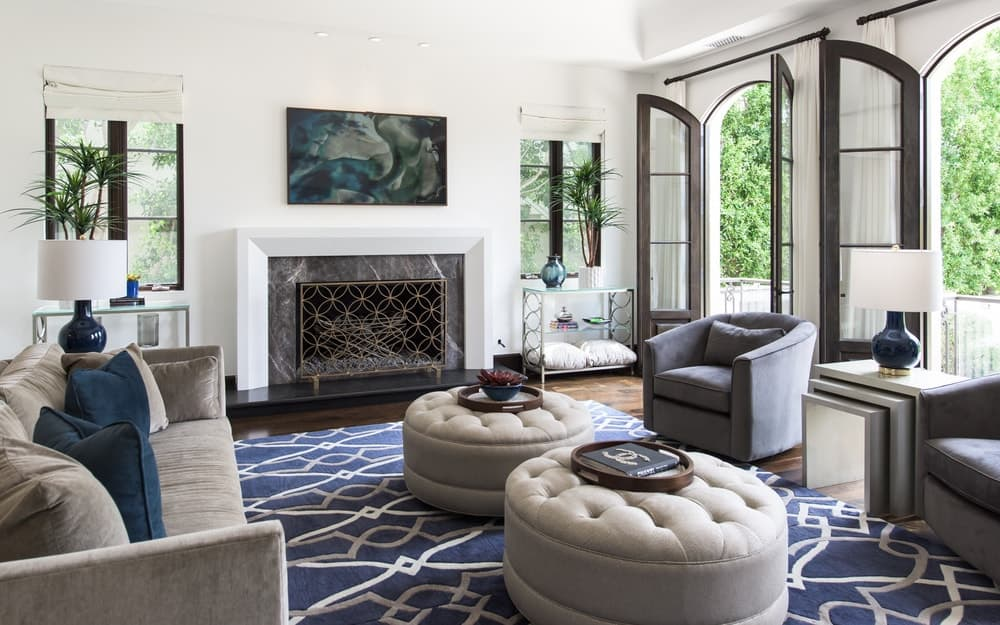 This view of the family room showcases the fireplace at the far wall with a white mantle that blends with the walls contrasted by the dark hardwood flooring. Image courtesy of Toptenrealestatedeals.com.