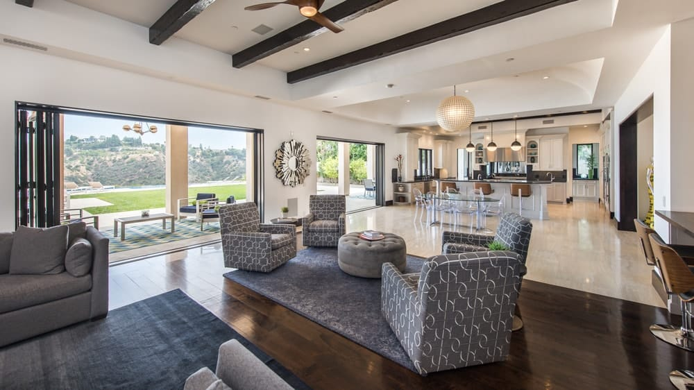 This is another view of the family room under a beamed ceiling and has large wall openings that lead to the covered patio. Image courtesy of Toptenrealestatedeals.com.