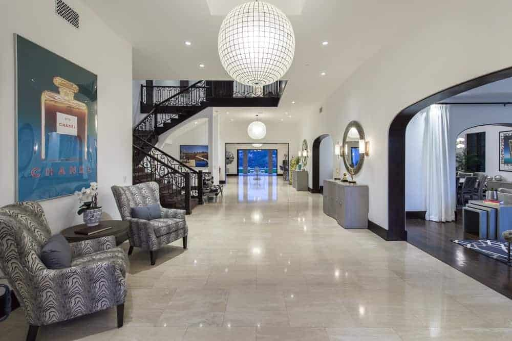 Upon entry of the mansion, you are welcomed by this foyer with marble floors, a large spherical pendant light, a couple of cushioned armchairs and a large painting on the wall. Image courtesy of Toptenrealestatedeals.com.