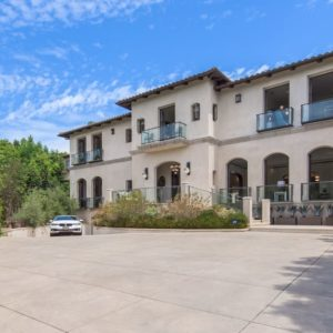 This is a front view of the mansion with beige exterior walls adorned by the tall arches, large balcony doors and glass balcony railings. There is also a wide driveway and courtyard in front of the house. Image courtesy of Toptenrealestatedeals.com.