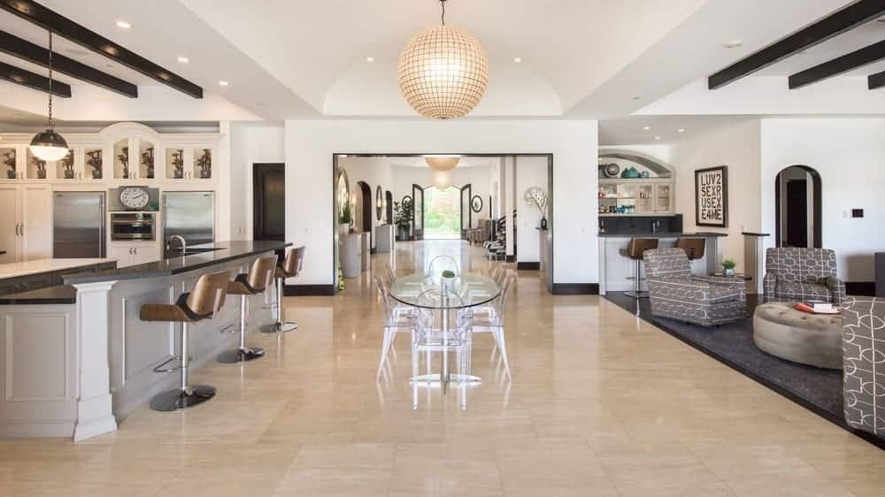 This is the spacious hallway in between the family room and the kitchen fitted with a glass table topped with a large spherical pendant light that hangs from the beige cove ceiling. Image courtesy of Toptenrealestatedeals.com.
