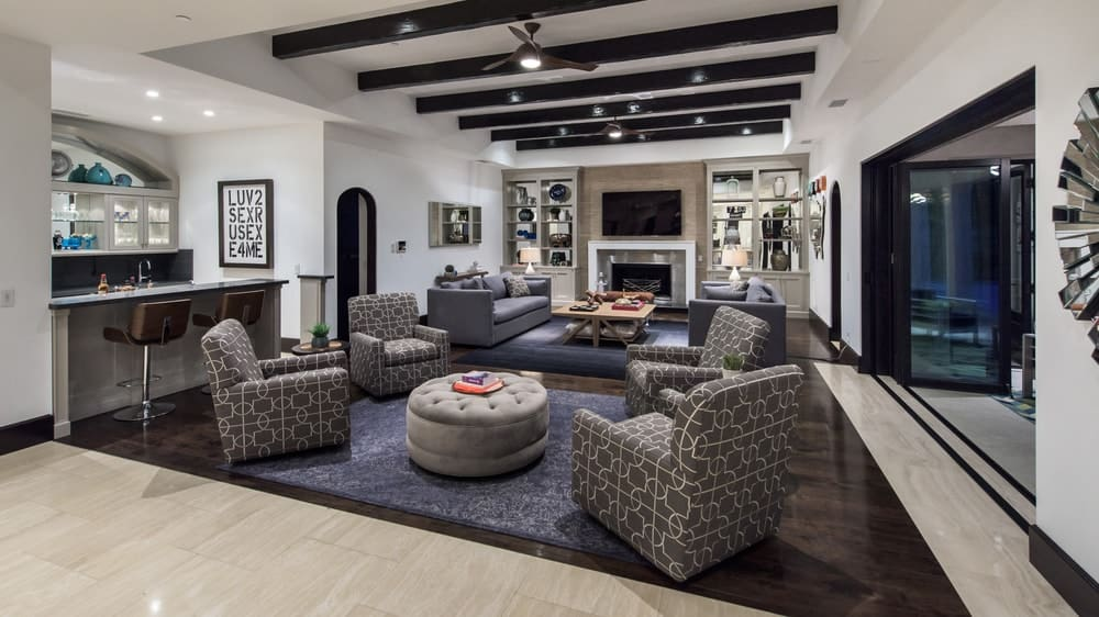 This is the spacious living room with sets of sofas and cushioned armchairs under a beamed ceiling. There is also a small wet bar on the side paired with a couple of stools. Image courtesy of Toptenrealestatedeals.com.