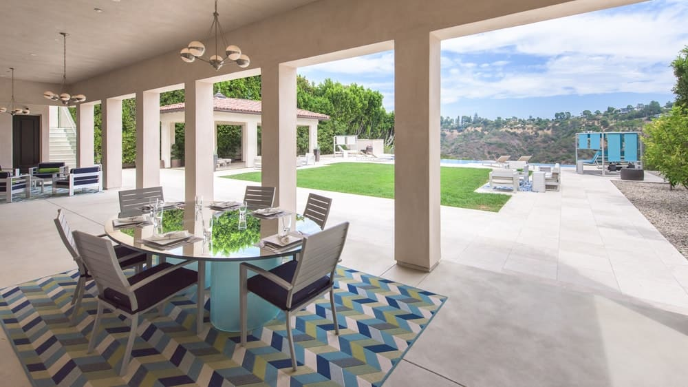 This is the covered patio at the side of pool area. This is supported by a row of pillars and open walls to brighten the glass-top outdoor dining set and outdoor kitchen. Image courtesy of Toptenrealestatedeals.com.