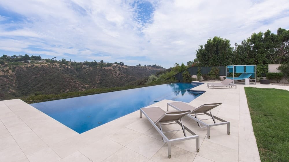 This is a closer look at the infinity-edged pool at the far end of the backyard with a sweeping view of the mountains. There's also a couple of lounge chairs at the side of the pool to better enjoy the scenery. Image courtesy of Toptenrealestatedeals.com.