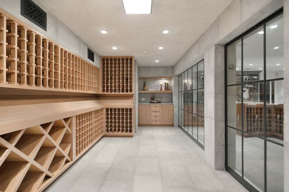 This is the 1,000-bottle wine cellar with large built-in wooden structures for wine storage. Across from these are a couple of French glass doors. Image courtesy of Toptenrealestatedeals.com.
