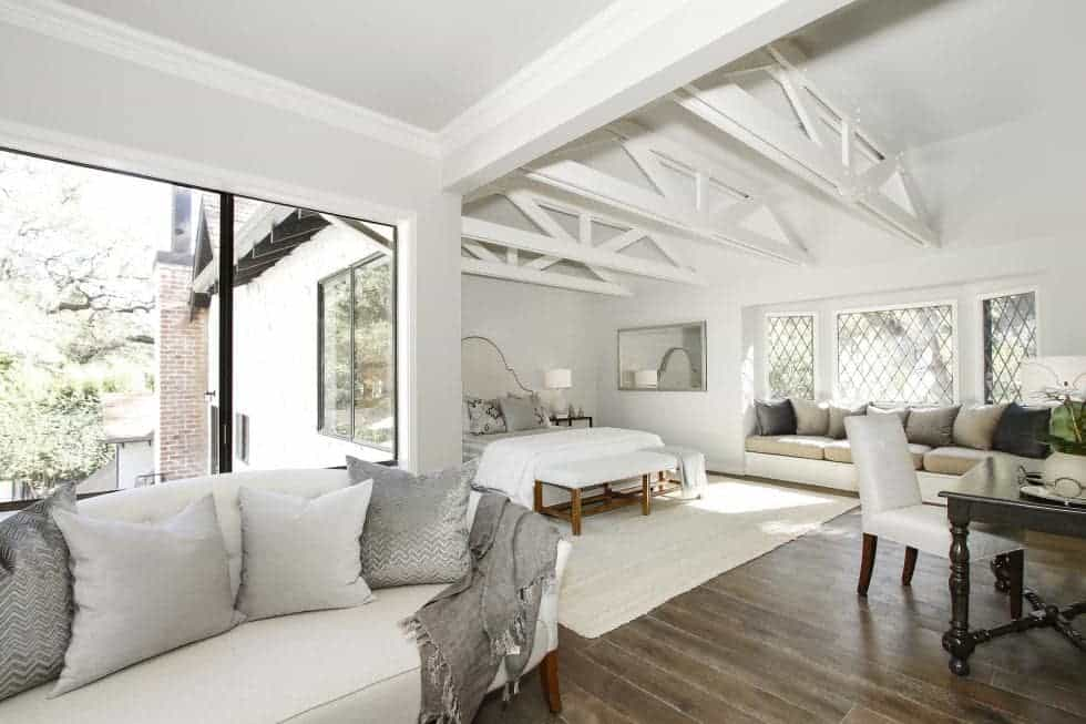 The spacious bedroom has a large bed in its own large alcove on the far side. This is complemented by the beamed cathedral ceiling, a sitting area and a reading nook by the window. Image courtesy of Toptenrealestatedeals.com.