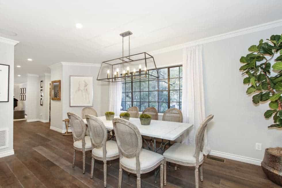 This is the dining area with a long white dining table surrounded by white cushioned chairs under a row of wrough-iron lighting that matches the frames of the window. Image courtesy of Toptenrealestatedeals.com.