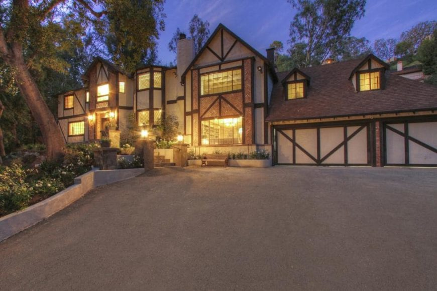 This is the front of the house featuring a wide concrete driveway leading to two garage doors that blend well with the exteriors of the house complemented by the large glass windows that glow warmly. Image courtesy of Toptenrealestatedeals.com.