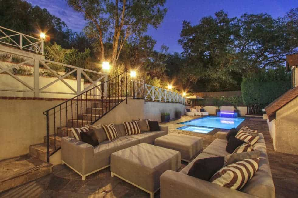 This is the backyard pool area with a large pool and spa and a large sitting area on the side that has sets of outdoor sofas and coffee tables. Image courtesy of Toptenrealestatedeals.com.