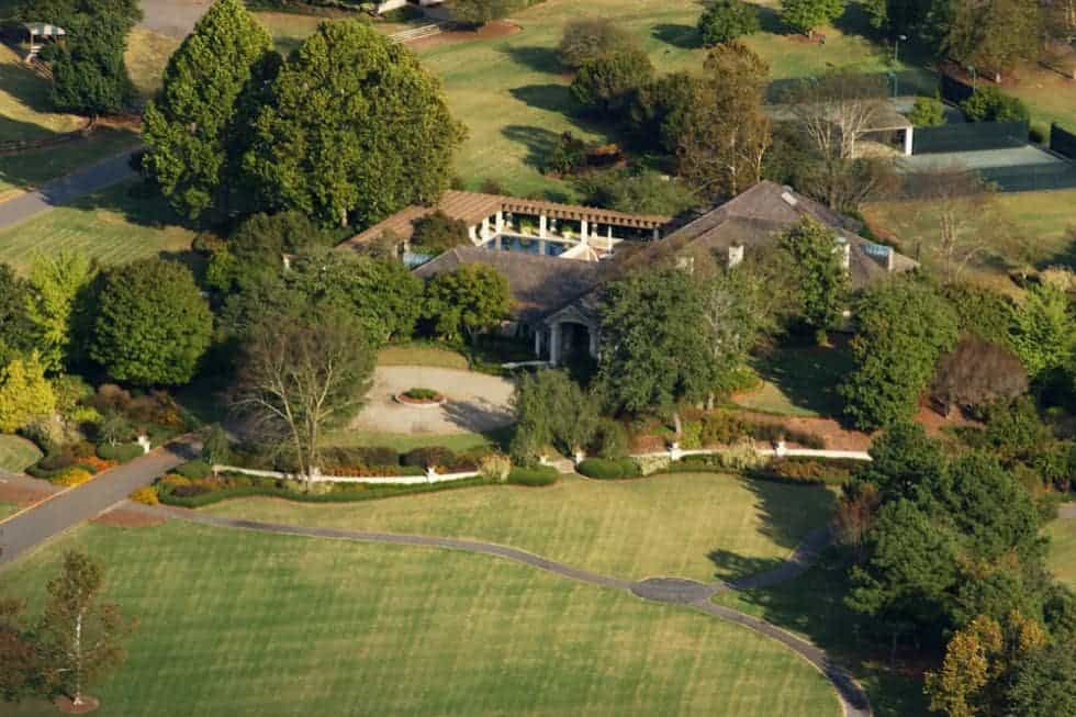 This is an aerial view of the main mansion with a clay roofs that stand out against the surrounding green landscaping with grass lawns, tall trees and thick shrubs. Image courtesy of Toptenrealestatedeals.com.
