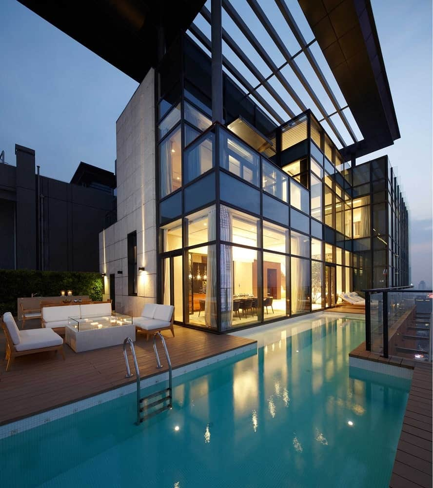 This is a view of the house from the vantage of the poolside area. You can see here that the house is mostly made of glass walls that glow warmly from the interior lights that escape to the wooden deck walkways outside.