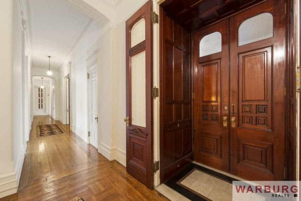 Upon entry of the apartment, you are welcomed by this simple foyer with wood paneled walls to match the main doors of the apartment. This also leads you to a long beige hallway. Image courtesy of Toptenrealestatedeals.com.