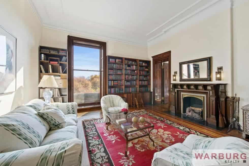 This is the library with built-in dark wooden bookshelves on the walls that blend with the wooden frames of the tall window and the mantle of the fireplace across from the sofa set and glass-top coffee table. Image courtesy of Toptenrealestatedeals.com.