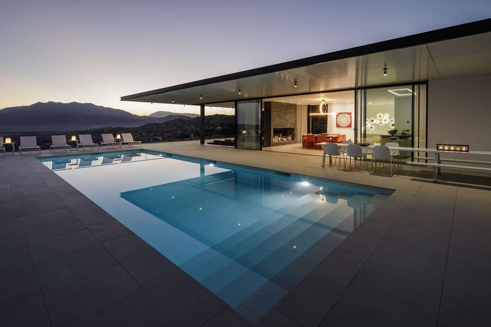 This is a view of the house from the vantage of the poolside area that is open to the interiors with glass walls that slide open. This area also has a sweeping view beyond the pool.