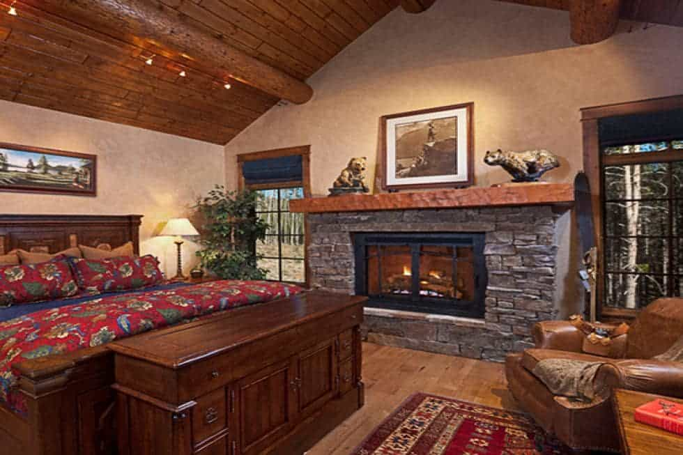 The primary bedroom has a large dark wooden bed warmed by a large stone fireplace on the side flanked by windows. Image courtesy of Toptenrealestatedeals.com.