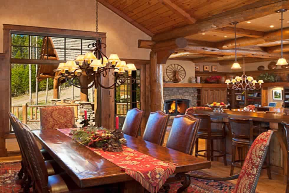 This is the dining area just a few steps from the kitchen. It has a large dark wooden dining table topped iwth a chandelier and surrounded by leather chairs. Image courtesy of Toptenrealestatedeals.com.