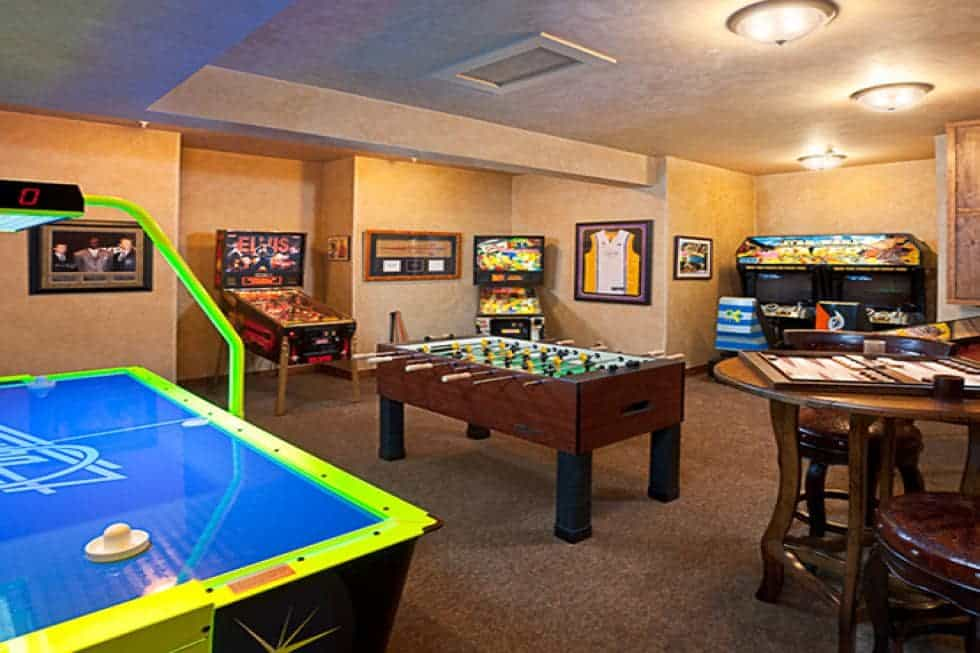 The large game room has various table games and arcade games that light up against the beige walls. Image courtesy of Toptenrealestatedeals.com.