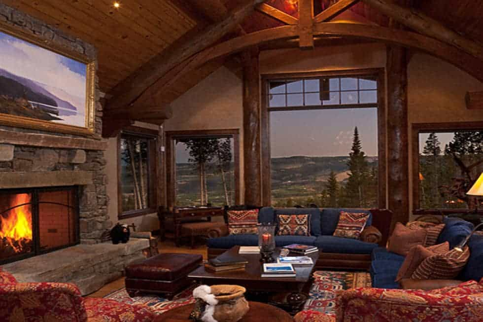 This is the living room that has a set of dark sofas warmed by the large stone fireplace. These are then complemented by the tall beamed ceiling and the large glass windows. Image courtesy of Toptenrealestatedeals.com.