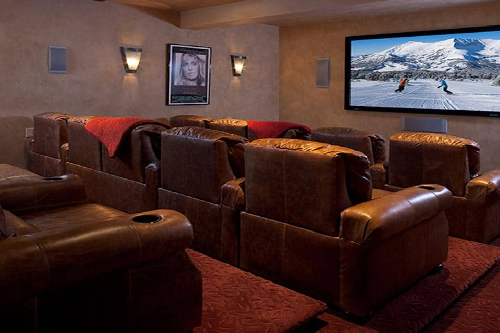 This is the luxurious home theater with rows of brown leather cinema chairs facing the large screen at the far end. Image courtesy of Toptenrealestatedeals.com.