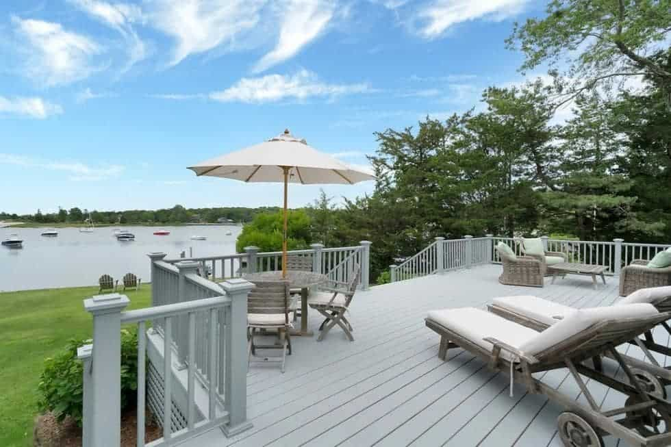 This is the spacious wooden deck overlooking the large grass lawn and the water scenery. This area is fitted with lounge chairs and an outdoor dining area. Image courtesy of Toptenrealestatedeals.com.