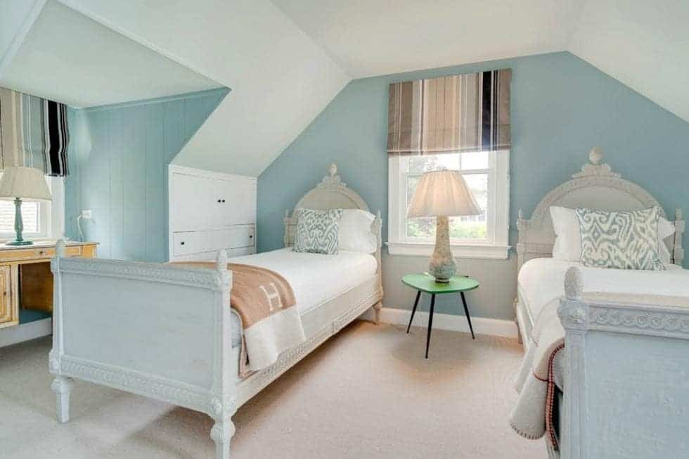 This other bedroom has two white wooden beds that pair well with the white ceiling and pastel tone of the walls. Image courtesy of Toptenrealestatedeals.com.