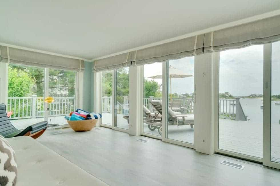 This is a look at the wrap-around deck of the cottage from the vantage of the interiors. You can see here that this is paired with glass doors that bring in natural lighting. Image courtesy of Toptenrealestatedeals.com.
