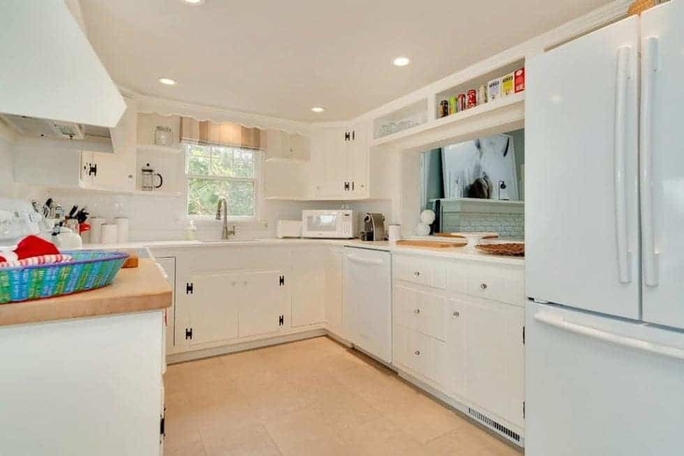 This is the bright kitchen with white cabinetry that blends with the walls and ceiling. These are then complemented by the beige flooring tiles. Image courtesy of Toptenrealestatedeals.com.
