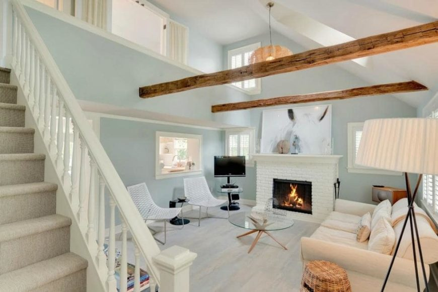 This is the cozy living room of the cottage with a tall ceiling adorned by the pair of exposed beams that stand out against the pastel tone of the walls. You can also see here the fireplace on the fa side that warms the sofa set. Image courtesy of Toptenrealestatedeals.com.