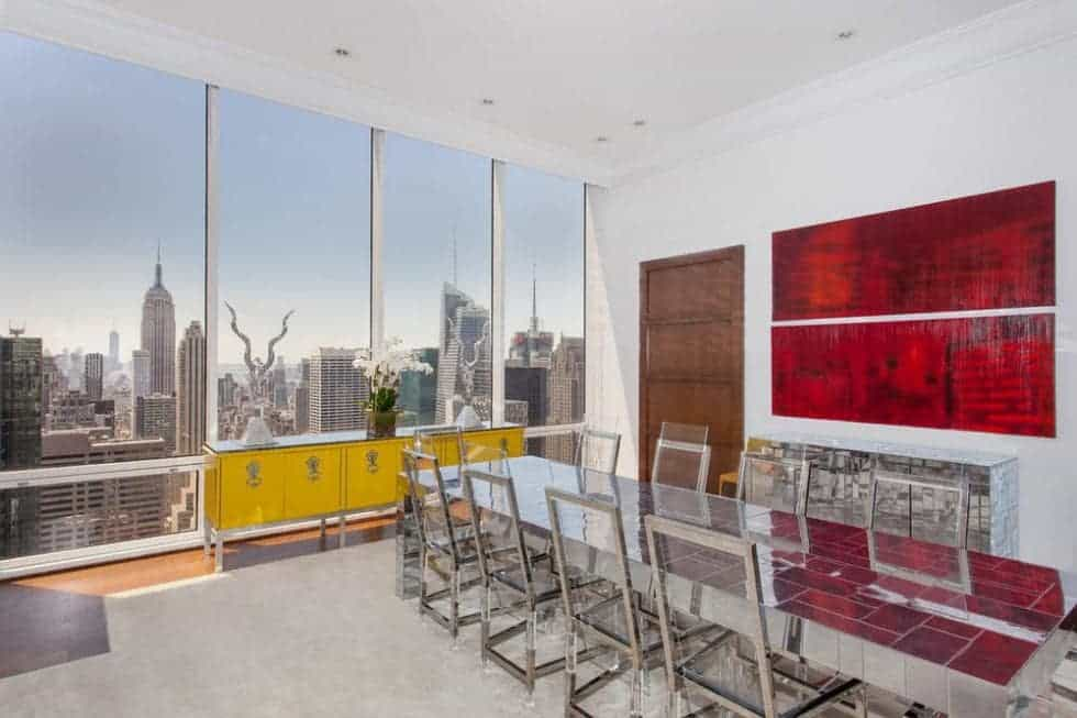 The dining room has a long glass-top dining table surrounded by modern steel chairs. The bright room is adorned with colors from the wall-mounted artwork and waist-high cabinet. Image courtesy of Toptenrealestatedeals.com.