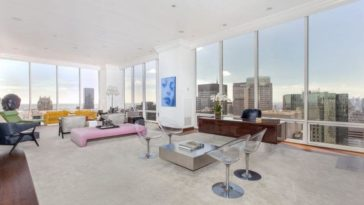 This is the great room of the penthouse with a recieving area and a living room area on the far side that are bathed in natural lighting from the glass walls. Image courtesy of Toptenrealestatedeals.com.