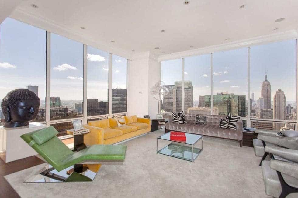 This is the living room area of the penthouse with colorful sofas and lounge chair pair with a glass coffee table. These are then complemented by the skyline view outside. Image courtesy of Toptenrealestatedeals.com.