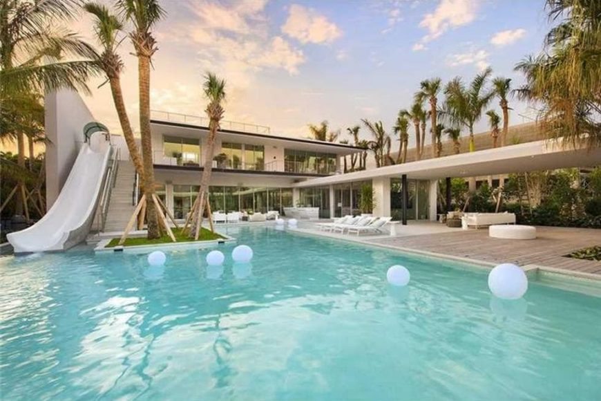 This is a view of the back of the house with a large waterslide connecting the second-floor primary bedroom terrace to the pool of the backyard. This side of the house also showcases the large glass walls and tropical landscaping. Image courtesy of Toptenrealestatedeals.com.