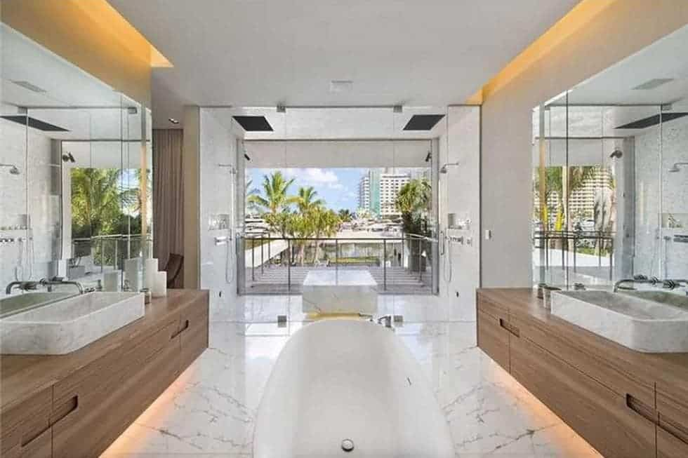 This is the bright white bathroom with a freestanding bathtub in the middle of two vanities. These are then brightened by the balcony on the far side. Image courtesy of Toptenrealestatedeals.com.
