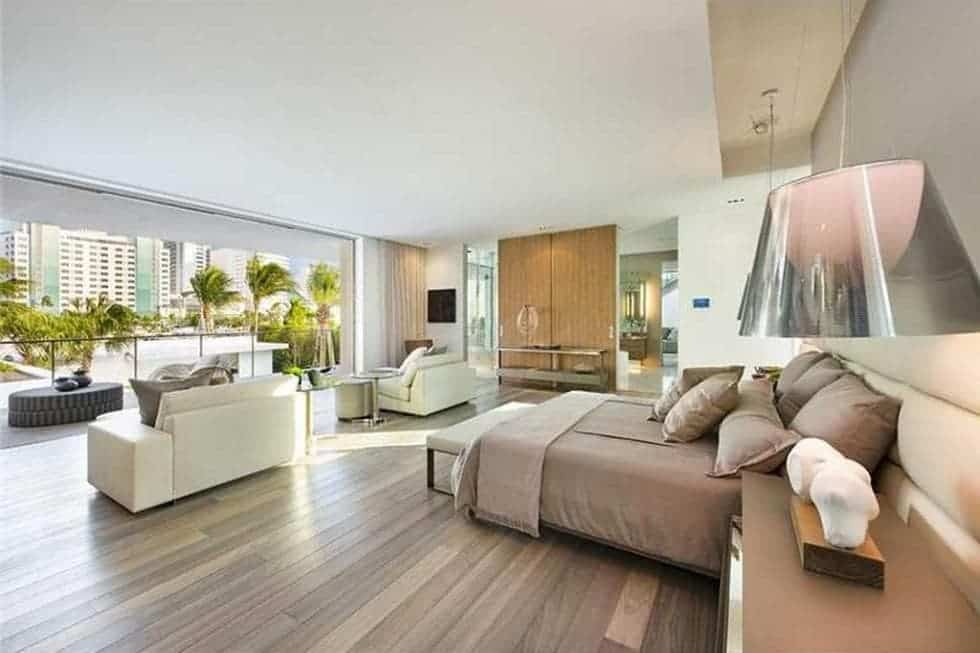 This is the primary bedroom with a hardwood flooring to match the bed and bright ceiling illuminated by the natural lights coming from the balcony. Image courtesy of Toptenrealestatedeals.com.