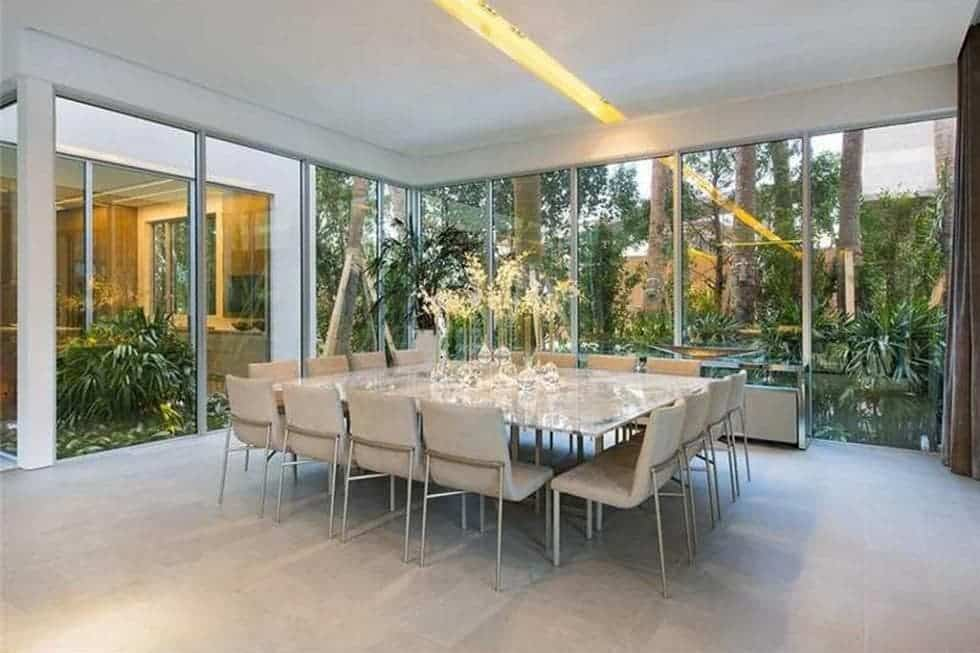 This is the spacious dining room with a large square table surrounded by beige chairs and complemented by the glass walls. Image courtesy of Toptenrealestatedeals.com.