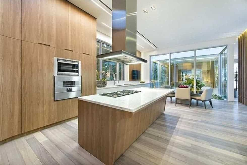 This is the large kitchen with a wooden kitchen island topped with a large stainless steel vent that matches the oven housed by the large wooden structure across from the island. Image courtesy of Toptenrealestatedeals.com.