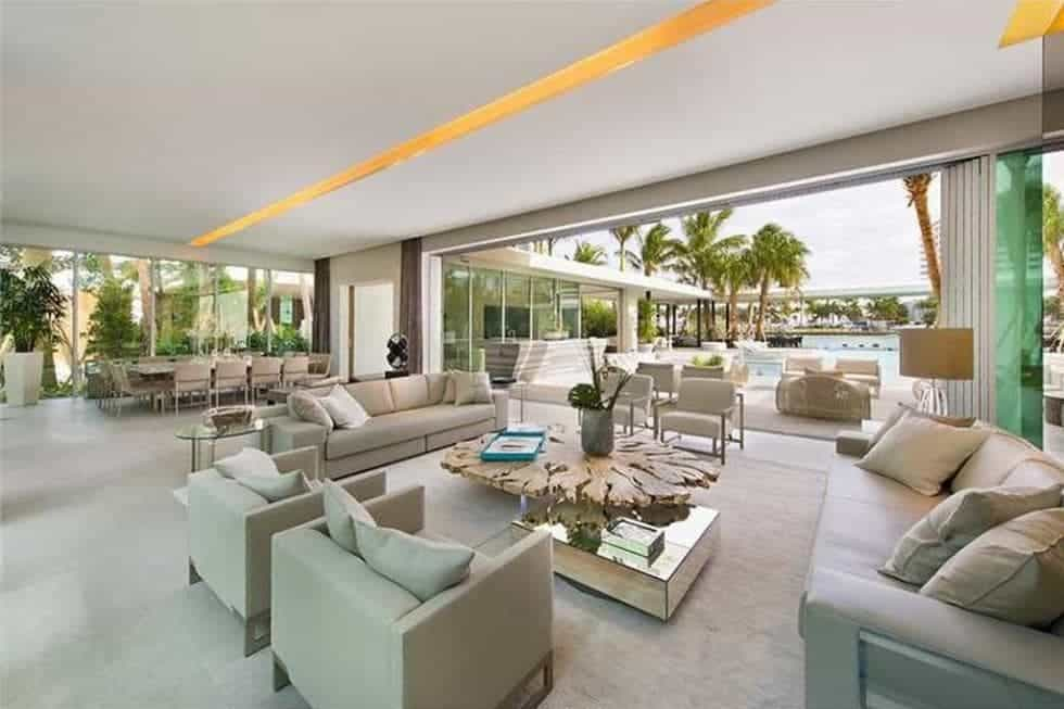 This is the spacious living room with sets of gray sofas and armchairs surrounding a rustic wooden coffee table. These are then complemented by the large wall opening that leads to the pool area. Image courtesy of Toptenrealestatedeals.com.