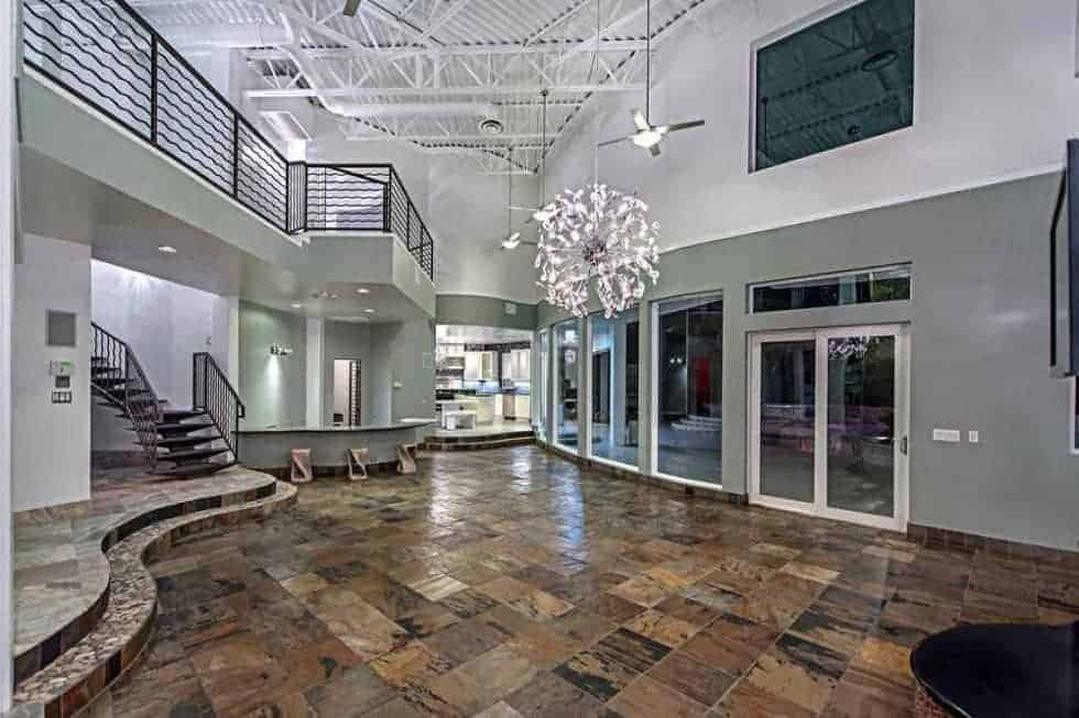 This is the great room with an earthy tone to its mosaic flooring topped with a large ornamental chandelier. You can also see here the kitchen on the far side and the indoor balcony above. Image courtesy of Toptenrealestatedeals.com.