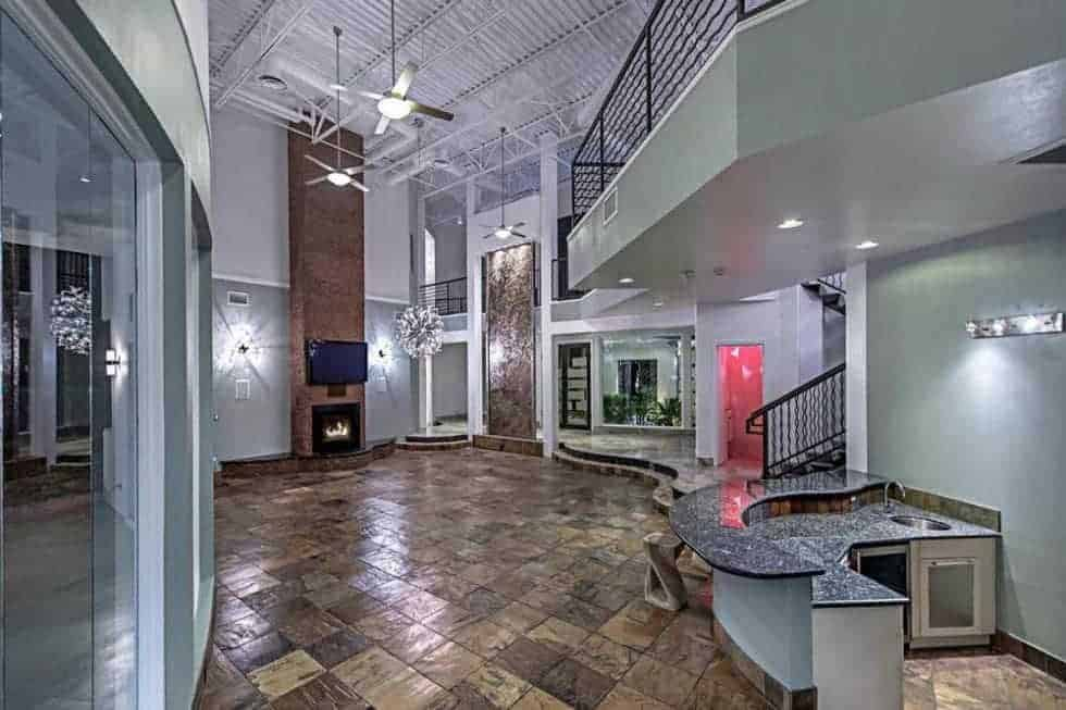 This is the other side of the large great room showcasing the fireplace on the far end as well as the tall Industrial-style ceiling. Image courtesy of Toptenrealestatedeals.com.