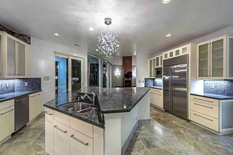 The spacious kitchen has a large kitchen island with a black countertop to contrast the white cabinetry. These make the stainless steel appliances. Image courtesy of Toptenrealestatedeals.com.