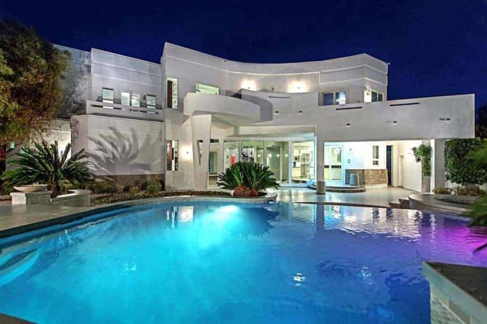 This is a look at the back of the bright house illuminated by the exterior and interior lights that complement the modern structures as well as the large swimming with its own lighting. Image courtesy of Toptenrealestatedeals.com.