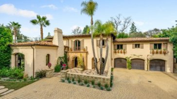 This is an aerial view of the front of the Tuscan-style house that has an earthy tone to its exterior walls, brick driveway and clay roof. These are then complemented by the surrounding lush landscape. Image courtesy of Toptenrealestatedeals.com.