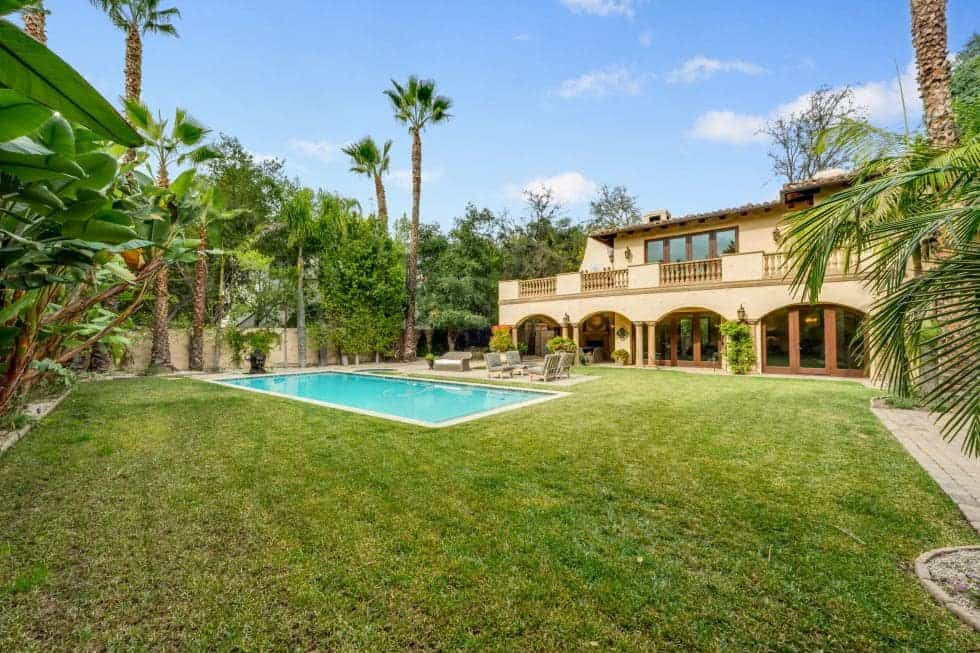 This is the back of the house with a large grass lawn that surrounds the swimming pool. You can also see here the tall trees that complement the beige earthy exteriors of the house. Image courtesy of Toptenrealestatedeals.com.