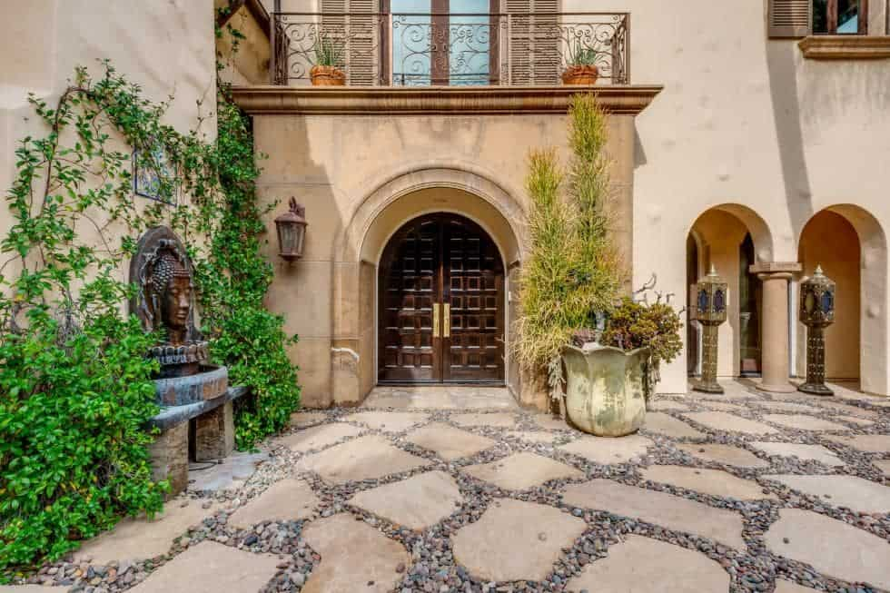 This is a close look at the main entrance of the house with an arched entryway fitted with dark wooden double doors. This is then complemented by creeping plants and potted plants on both sides. Image courtesy of Toptenrealestatedeals.com.