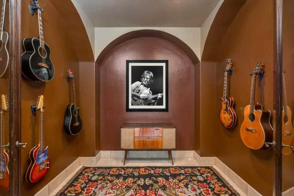 This is the guitar display room with various guitars mounted on the dark brown walls with arches and alcoves. Image courtesy of Toptenrealestatedeals.com.