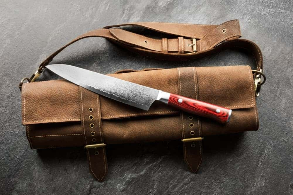 Japanese chef's knife on top of a brown leather bag.