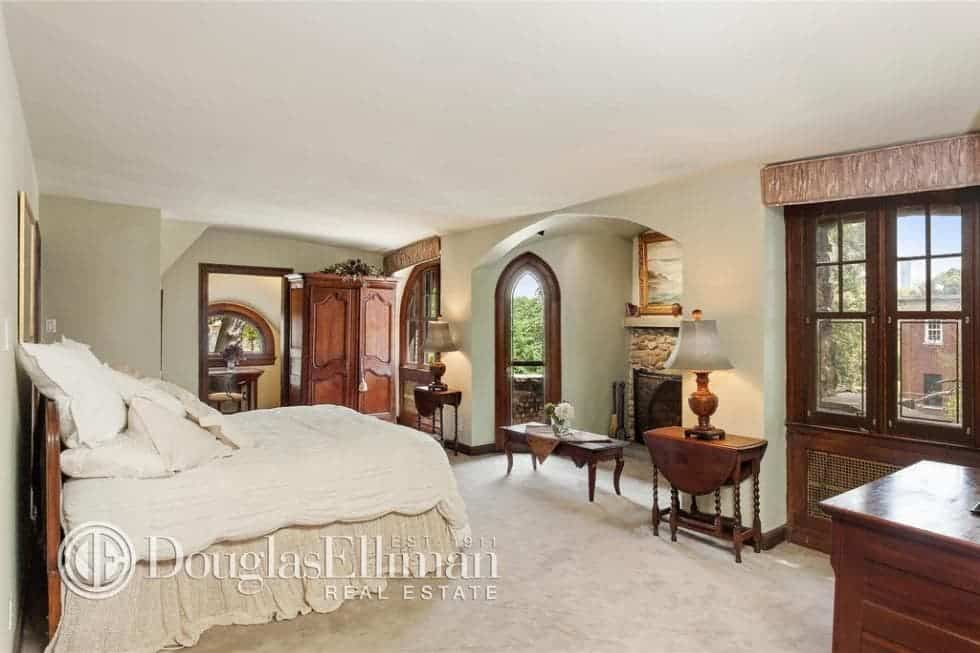 This is a bright and airy bedroom that has beige walls, ceiling, bed and floor. These are then complemented by the surrounding various dark wooden elements. Image courtesy of Toptenrealestatedeals.com.