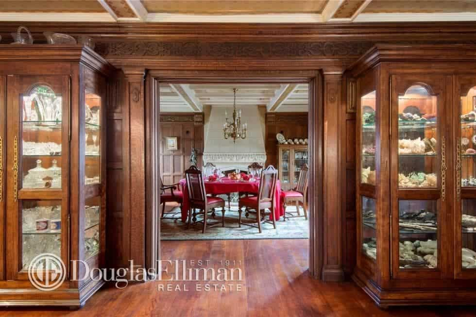 This is the entryway that leads to the formal dining room that has a large dining table. The dark hardwood flooring matches well with the wood-paneled walls and furniture. Image courtesy of Toptenrealestatedeals.com.
